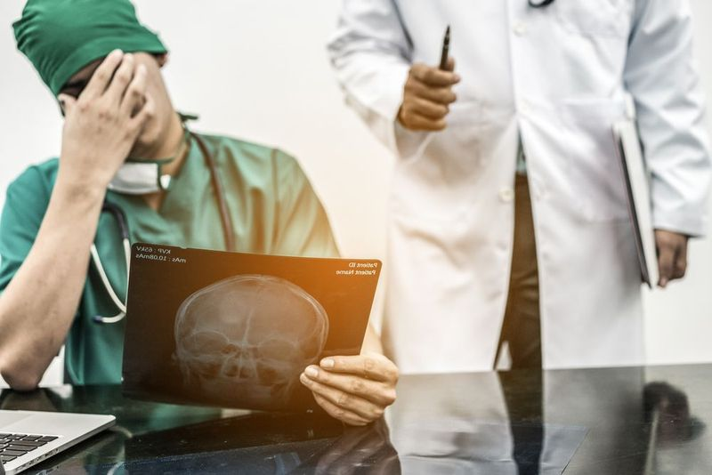 Upset surgeon holding x-ray with hand over eyes