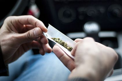Close view of hands rolling marijuana into papers,