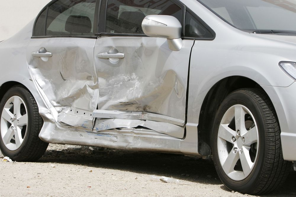 A silver car with accident damage on the passenger-side door