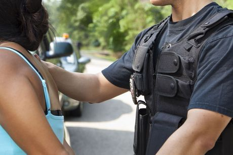 A woman being handcuffed b y a police officer