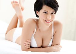 Dark-haired woman in underwear lying on the bed