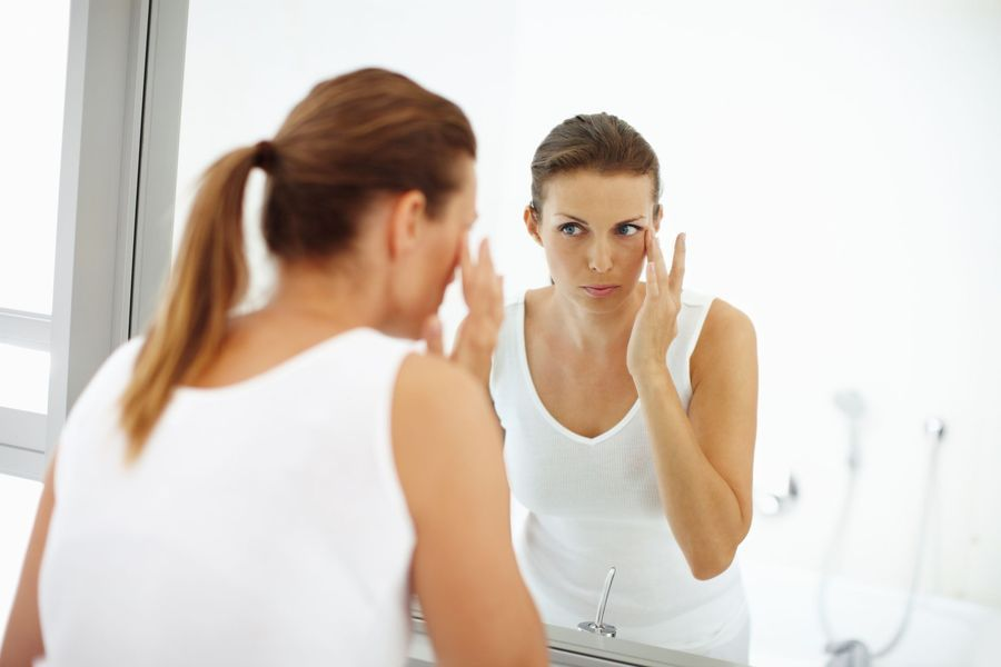 Woman looking in mirror and applying face cream