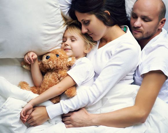 Couple sleeping peacefully with little girl