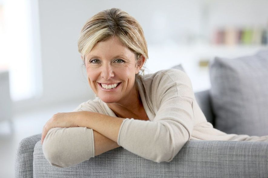 Smiling woman leaning over back of couch