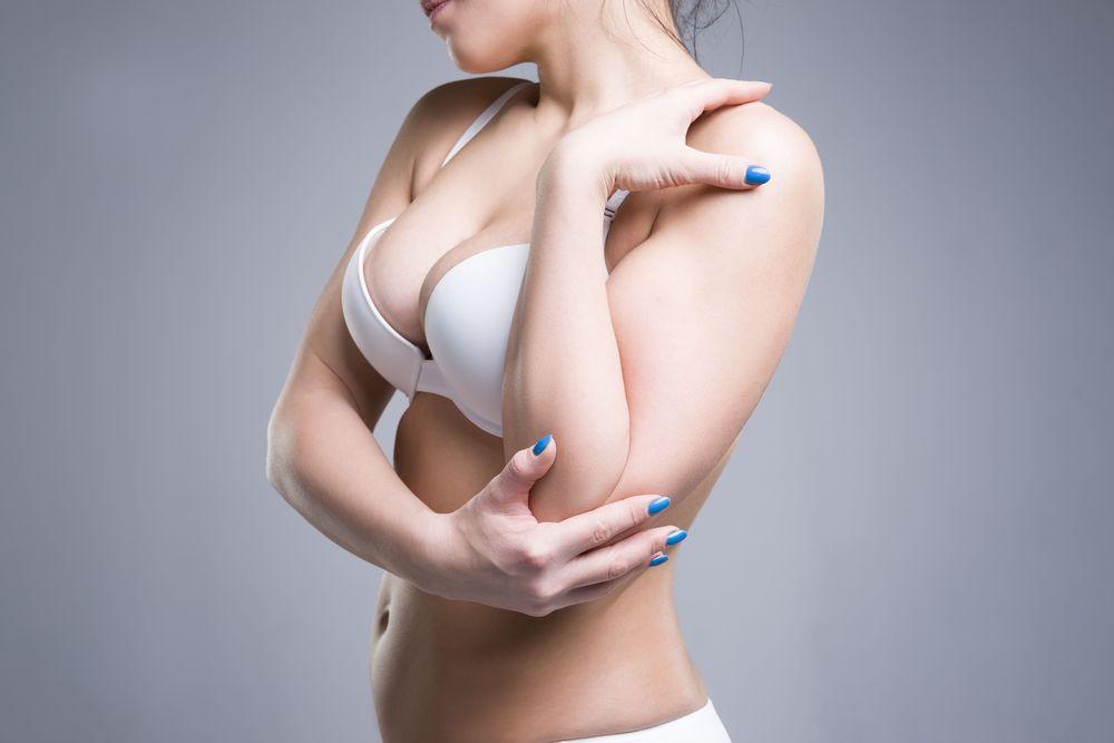 A woman wearing a white bra and blue nail polish.