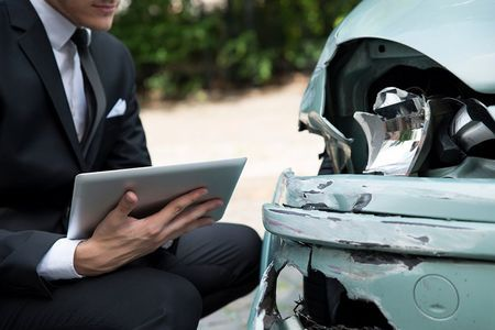photo of a man in a suit next to a damaged car