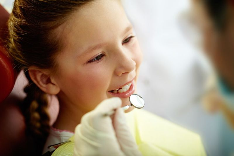A young child undergoing a dental exam and cleaning.