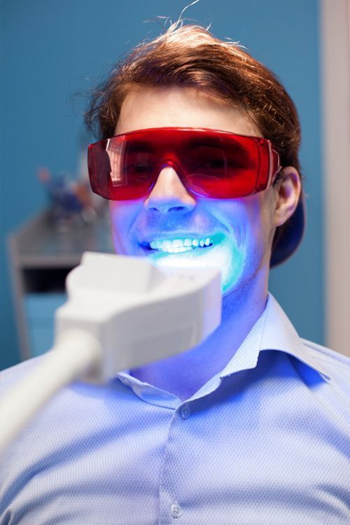 Man with eye protection getting laser teeth whitening