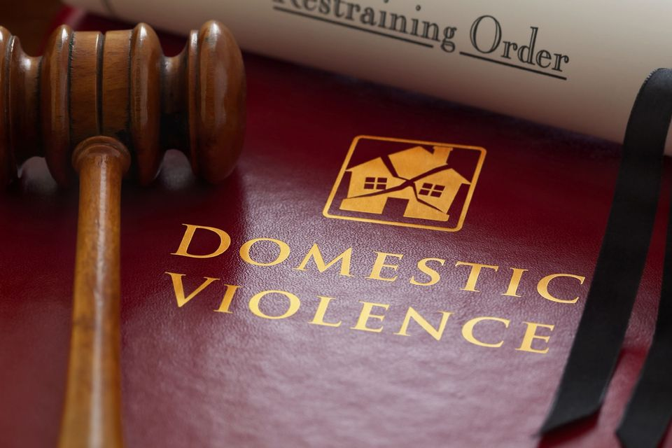 Domestic abuse book, gavel, and restraining order paperwork
