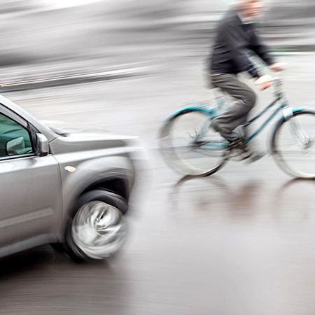 A blurry photo of an oncoming car and a bicycle