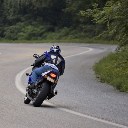 A motorcyclist driving down a road
