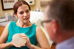 A female patient holding a breast implant while talking to her doctor