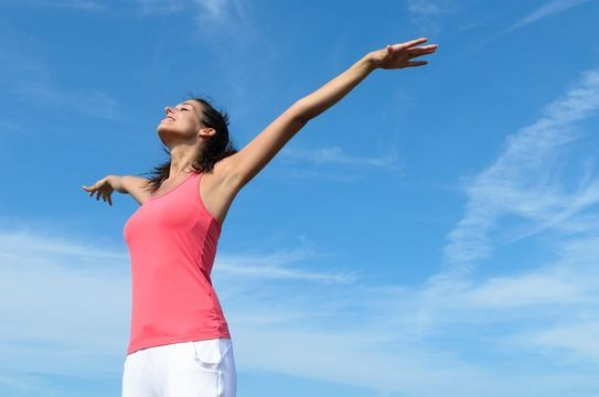 Woman standing under a blue sky with her arms open