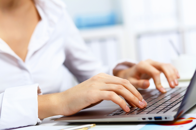 Photo of a person typing on a computer