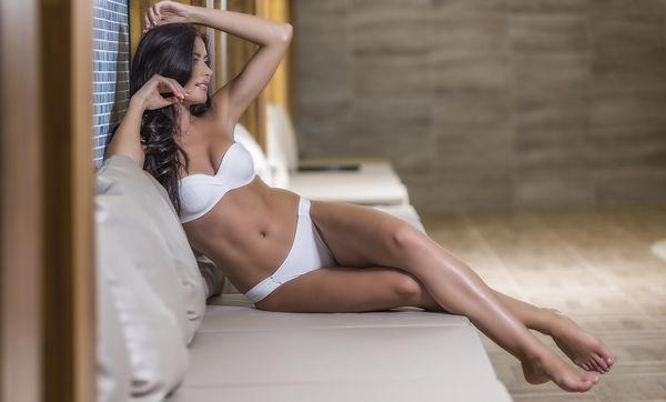 A brunette woman in white underwear reclines in a chair