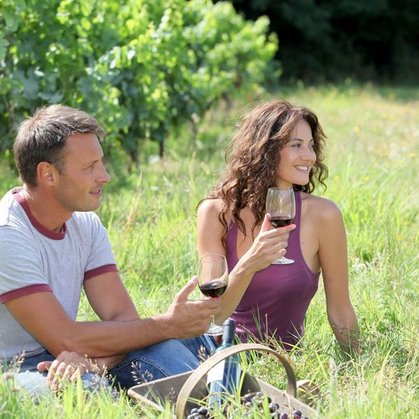 Man and woman sitting in grass with wine