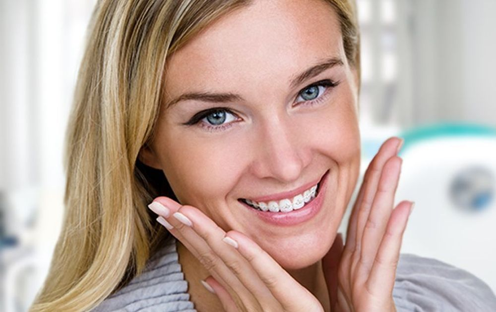 Woman wearing clear braces with her hands to her cheeks