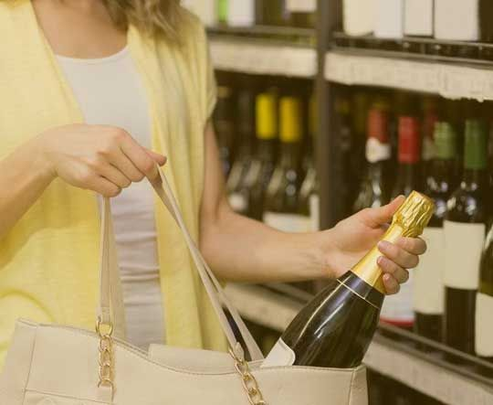 A woman putting a champagne bottle into her purse
