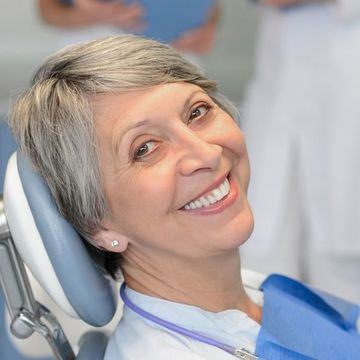 Woman in dentist chair, smiling.
