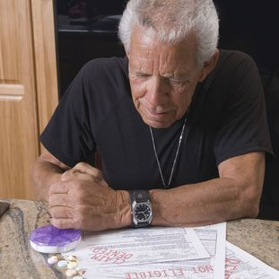 Concerned older man looking over denied health claims paperwork