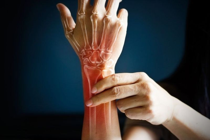 Woman holding arm showing digital image of tendons and bone