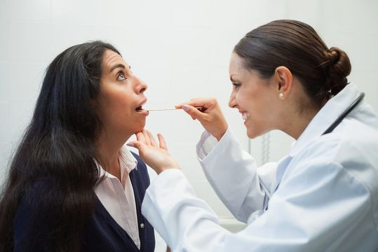 A doctor looking into a female patient's mouth