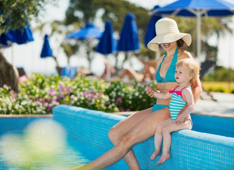 Woman and toddler sitting at the edge of a pool