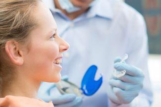 Image of smiling girl receiving a dental aligner