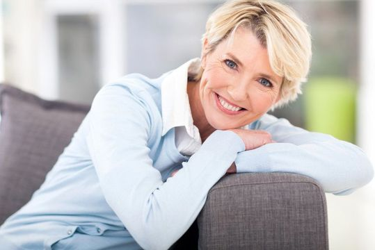 Smiling woman with short blond hair resting arms over side of a couch