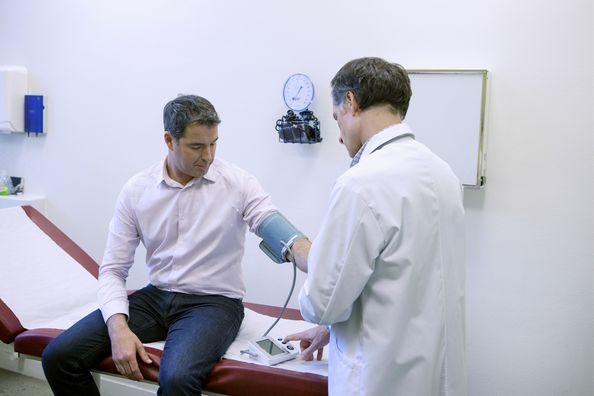 A well-dressed man has his vital signs taken by a doctor.