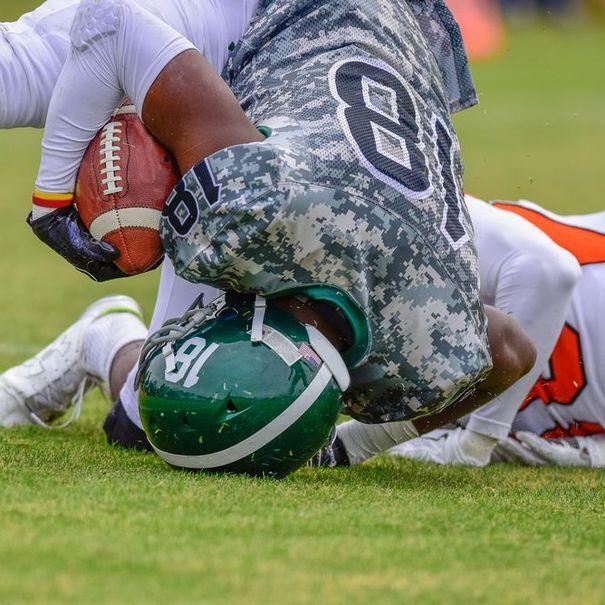 Football player landing on his head.