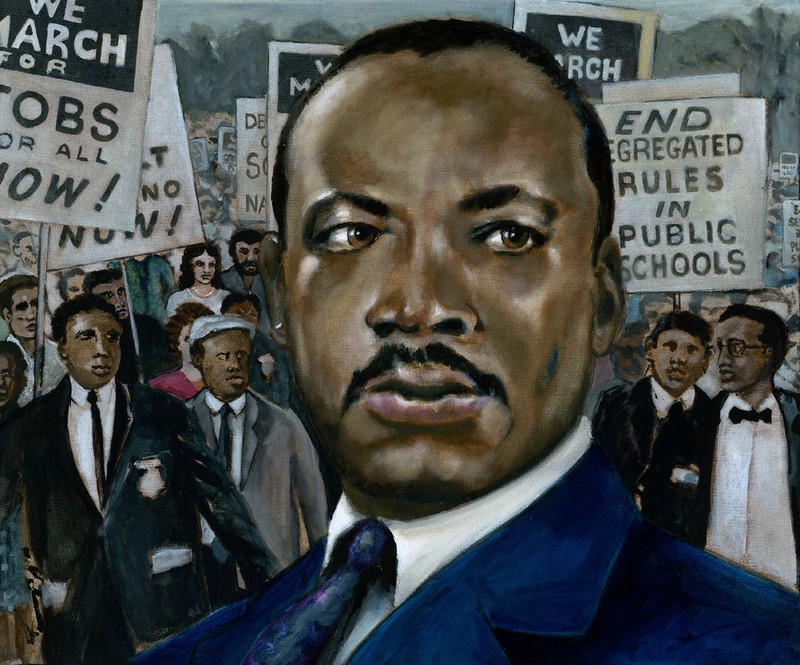 Portrait of Martin Luther King Jr. in front of a crowd of protestors.