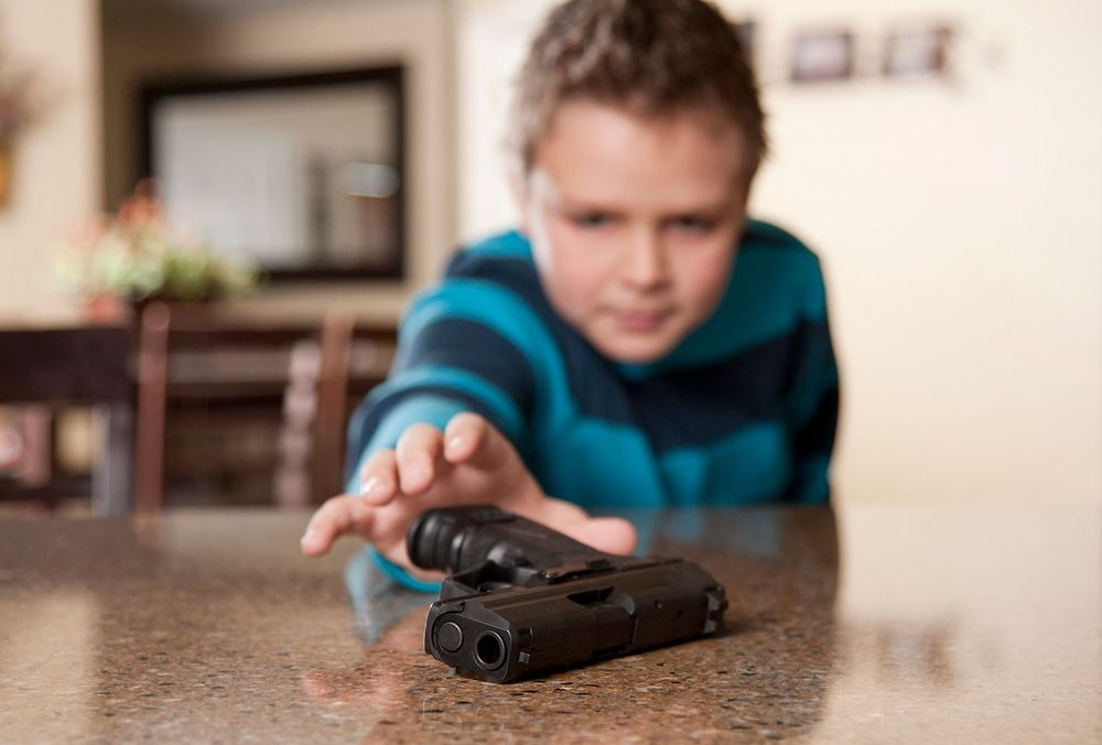Child reaching for handgun on counter
