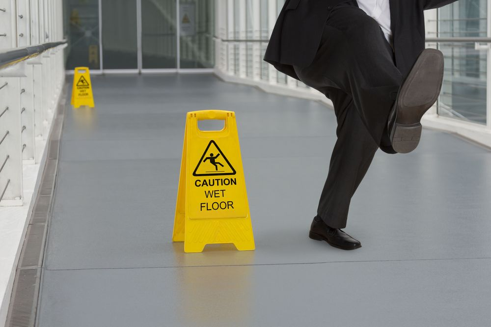 A man in a suit slips near a wet floor sign