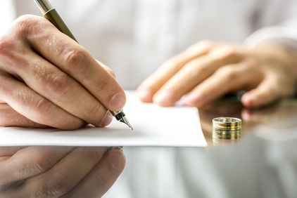 Photo of hand signing paper next to a wedding band
