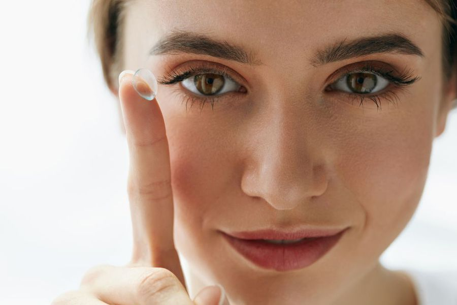 Woman holding contact lens on fingertip