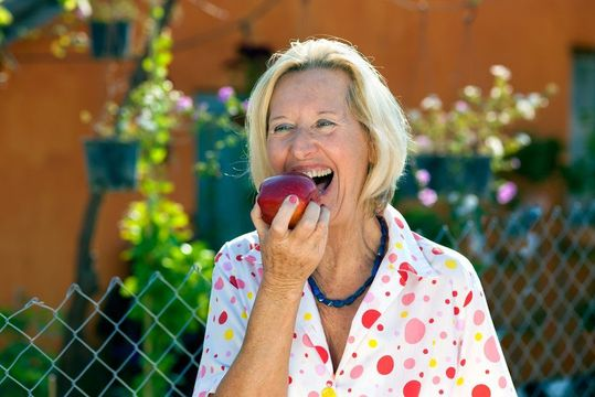 An older woman taking a bite from an apple