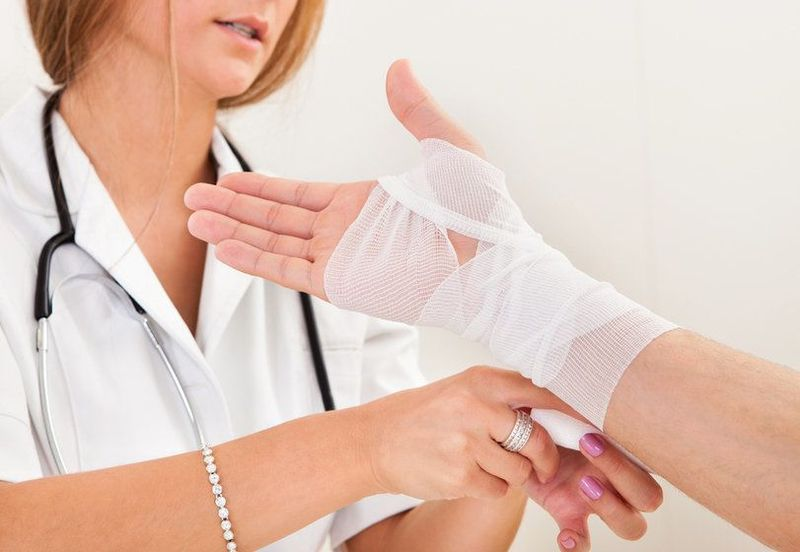 Female medical practitioner wrapping hand in gauze