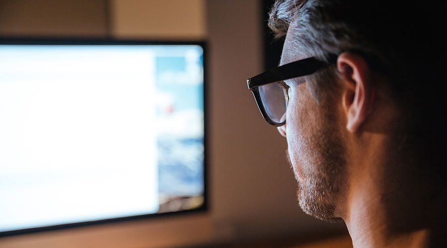 Photo of a man in glasses looking at a computer screen