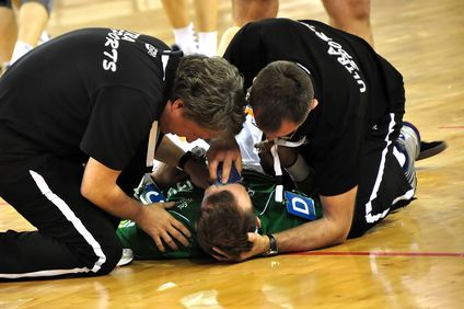Referees attending to basketball player laying on court