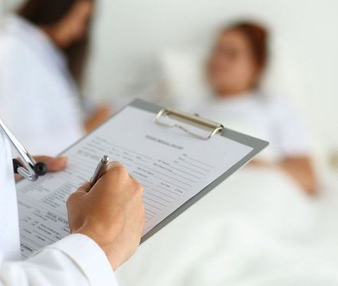 Health practitioner writing on clipboard in front of blurred patient in hospital bed