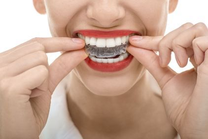 Woman placing dental appliance.