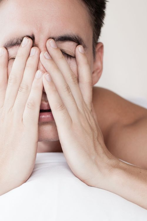 Photo of a man with hands on his face tired