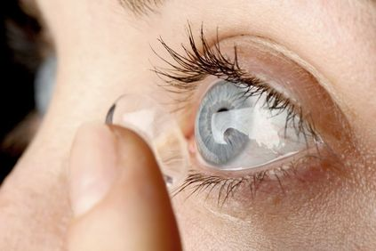 Close-up of woman putting in a contact lens