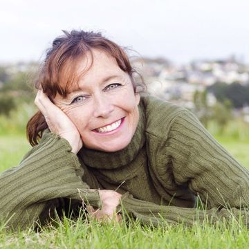 A smiling woman lying on the grass