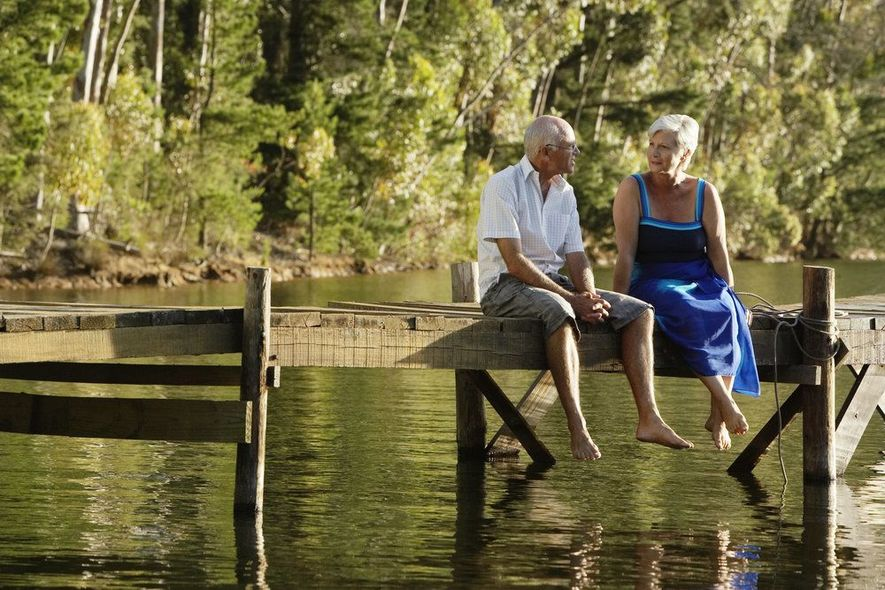 Two white-haired folks sitting on a dock above a lake.
