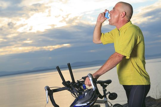 Male cyclist using an inhaler
