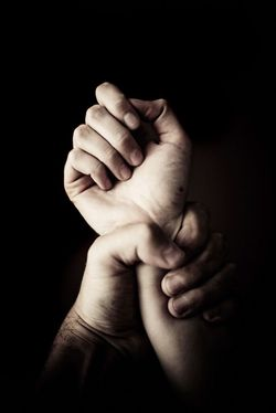 A person gripping their own wrist with a black background