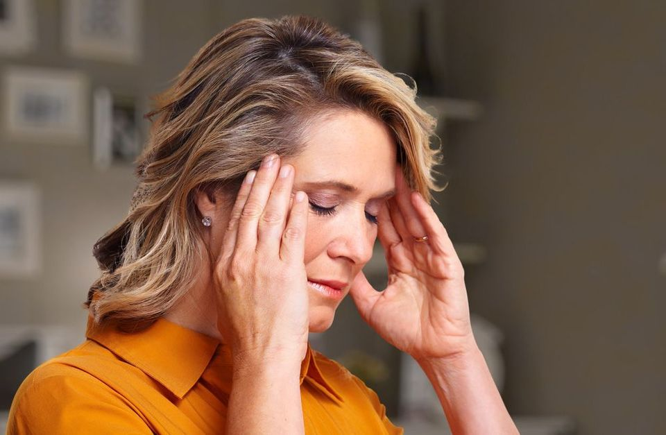 Photo of woman holding head in pain
