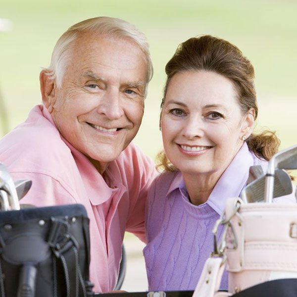 Older couple smiling in golf cart